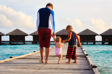 father with kids walking on tropical resort