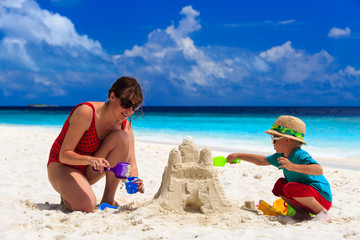 mother and son building castle on the beach