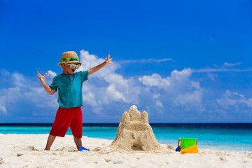 happy child with built sand castle on the beach