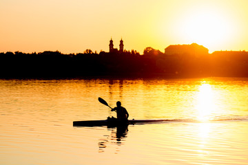 Enjoy sunset - man kayaking on lake