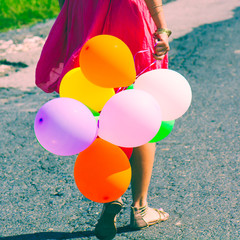 girl holding bunch of colorful air balloons