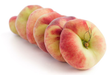 Group of ripe flat peaches on white