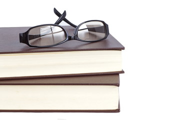 Glasses and reading book on white background