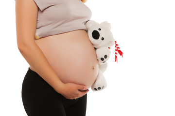 Mom in pregnancy holding a teddy bear. isolated on white