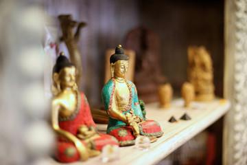 Two Buddha statues on shelf of souvenir shop