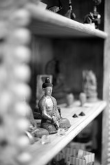 Buddha souvenirs on a shelf, monochrome