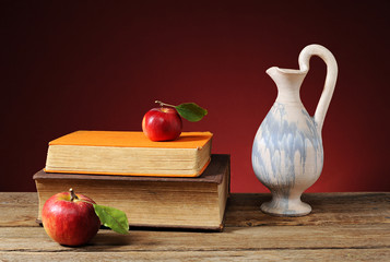 Apple, books and ceramic jug