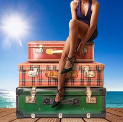 ragazza seduta sopra valigie vintage