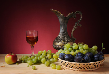 Grapes, apples, wine and metal carafe on the table