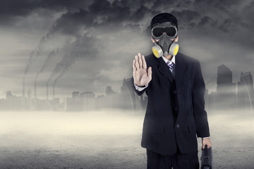 Pollution concept: businessman in a gas mask