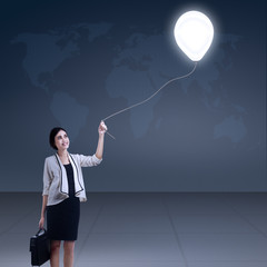 Businesswoman holds bulb balloon