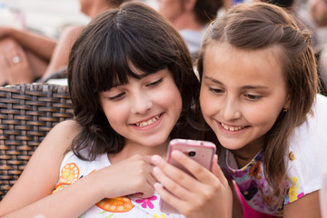 Two girls with smartphone smiling