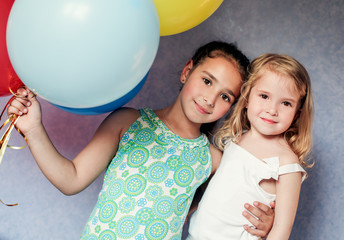cute sisters with colorful balloons