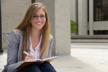 Cheerful, attractive young woman with journal