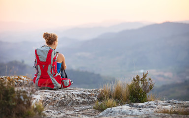 Woman tourist sitting on top of a mountain