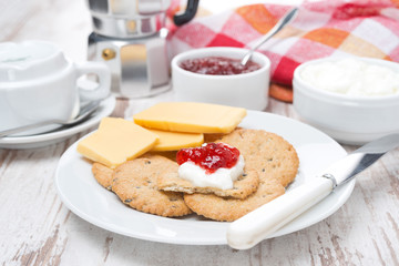 crackers with cheese, cream and jam for breakfast