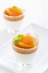 dessert with cream and apricot jelly in glasses on plate