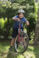 Vertical image of little child on bike looking at camera