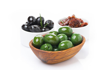 green and black olives, sun-dried tomatoes in a bowls, isolated