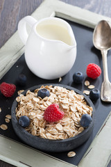 healthy food - cereal, fresh berries and jug of milk, close-up