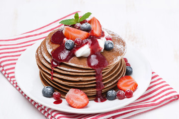 pancakes with cream and berries on a white wooden table, closeup