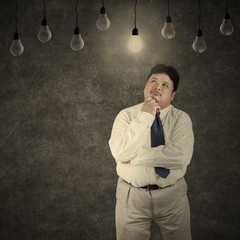 Fat businessman looking at bright lightbulb