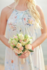 Beige and white wedding bouquet of roses in the hands of the bri