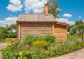 Log house in the garden among the flowers