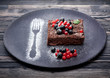 Chocolate cake brownie with summer berries on dark background