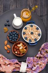 Oat flakes, blueberries, nuts, honey and milk. Breakfast.