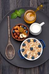 Muesli with raisins, nuts, honey, milk and blueberries.