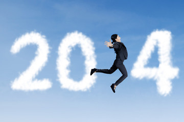 Happy businesswoman jumps with clouds of 2014