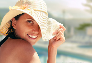 Smiling woman in big summer hat near the pool