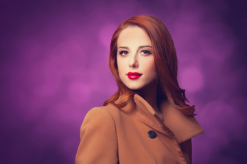 Redhead women in coat on vilolet background.