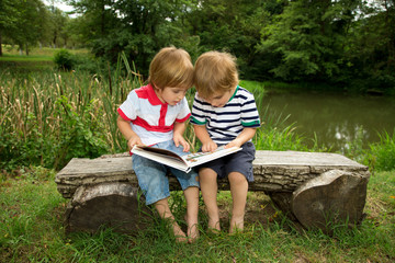 Little Twin Brothers Reading a Book Very Carefully at the Lake