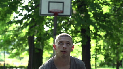 Man throwing free throw on court in park, super slow motion,