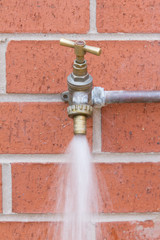 Outside tap on brick wall wasting water