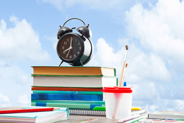books and an alarm clock on a wooden table on a white background
