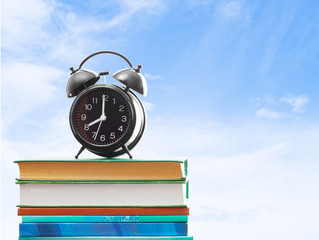 books and an alarm clock on a background of blue sky