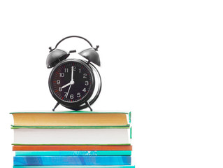 books and an alarm clock on a white background isolated