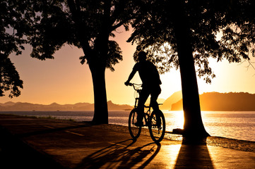 Silhouette of a Man Cycling during Beautiful Sunrise