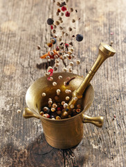 various spices falling into mortar and pestle