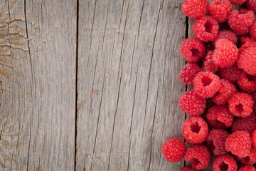 Fresh ripe raspberries on wooden table
