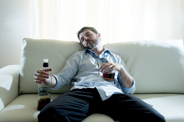 alcoholic Businessman in shirt and tie sleeping drunk on couch