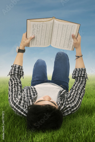 Student reads book outdoors