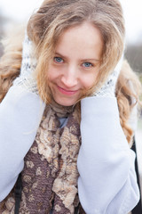 Portrait of a frozen happy young woman heated by wool mittens