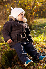 Cute child sitting on a stump