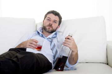 alcoholic Businessman drinking whiskey on couch