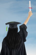 Woman in graduation gown rejoicing success
