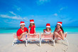 Family in santa hats having fun on tropical beach